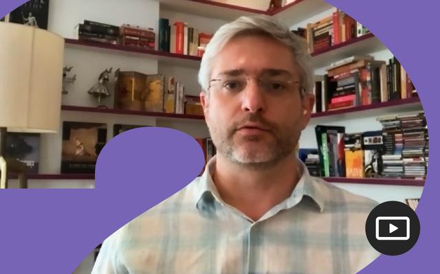 Captura do vídeo do médico Adriano Massuda, que aparece em frente a estantes com livros e itens de decoração vestindo camisa quadriculada branca e azul e óculos de grau.