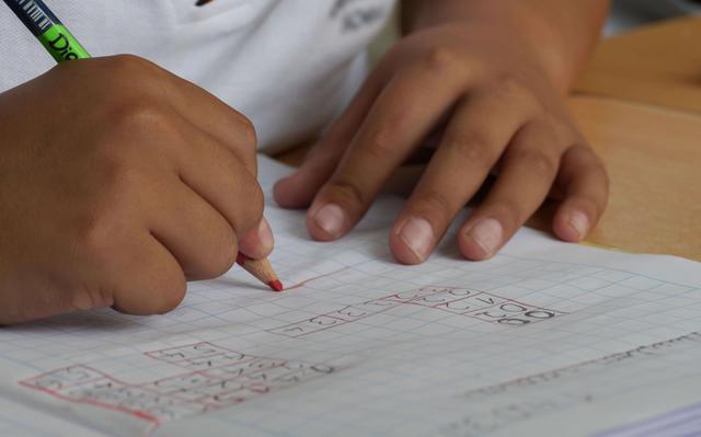 Imagem aproximada de mão de criança segurando lápis sobre caderno com contas de matemática