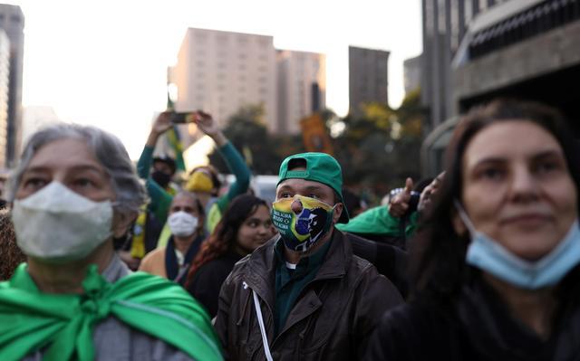 manifestantes pró-bolsonaro vestem roupas e acessórios com a bandeira do Brasil. destacam-se os rostos de três pessoas: uma senhora de cabelos brancos que olha para cima, usando máscara de proteção de forma adequada, com uma bandeira do Brasil amarrada nas costas, um homem que usa boné verde e um tipo de máscara com um furo na área do nariz, estampada com a foto do presidente bolsonaro sobre a bandeira brasileira, e uma mulher vestida de preto de usa a máscara de proteção sobre o queixo