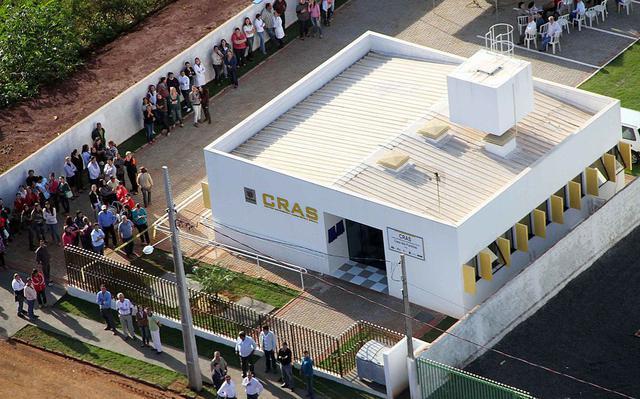 Vista aérea do CRAS Fênix, no Paraná.  Na lateral do estabelecimento uma fila de pessoas aguarda a abertura