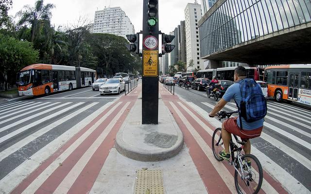 À direita, um homem anda de bicicleta sobre uma faixa vermelha pintada no asfalto. Ele está em uma área que é também de faixa de pedestres. Além dele, vê-se na foto um semáforo, outros carros e ônibus e parte da fachada do Masp.