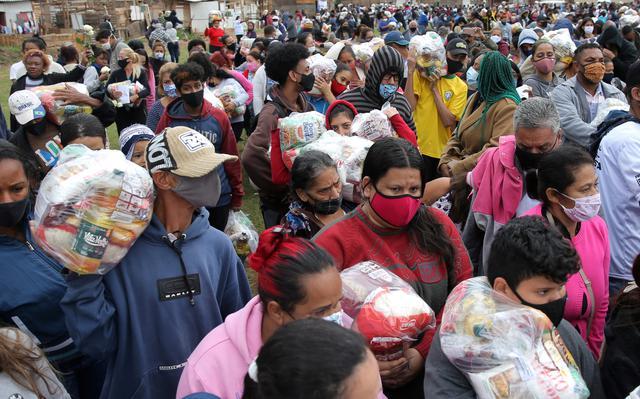 Pessoas de diversas idades vestindo máscara aglomeradas carregam sacos plásticos com alimentos da cesta básica. Ao fundo é possível ver moradias de madeira e outras com tijolos expostos.