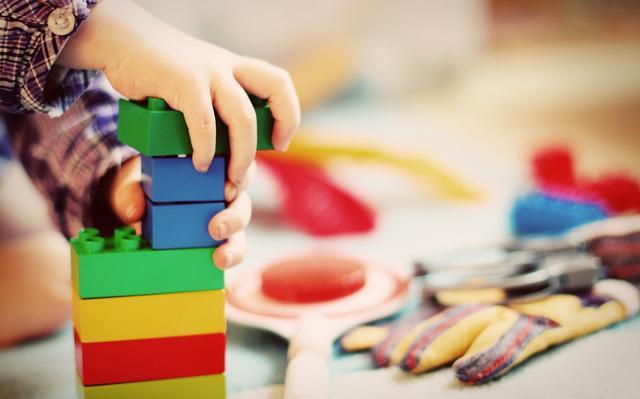 Mão de criança monta torre com blocos coloridos