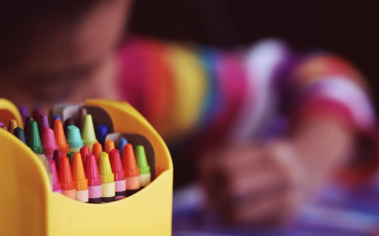 Em primeiro plano, uma caixa de giz de cera coloridos. Atrás, uma criança desenhando