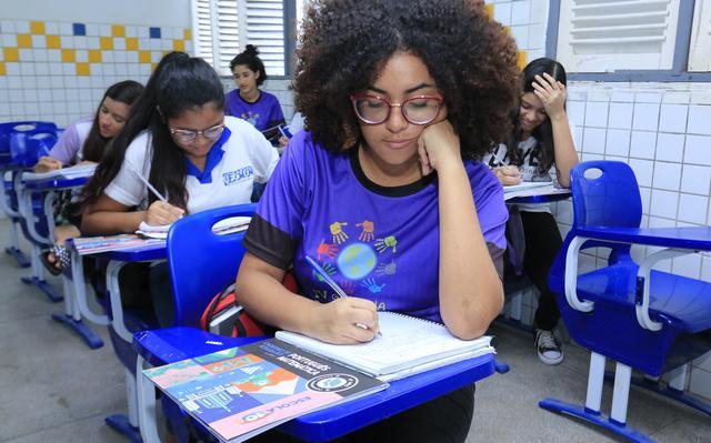 Estudante de camiseta azul sentada em carteira escolar anota em um caderno