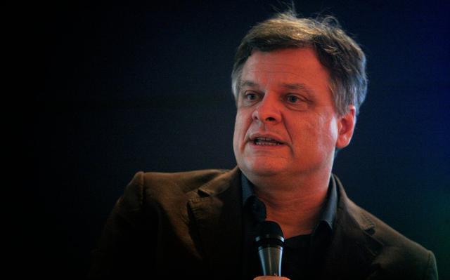 Foto de Fabio Scarano, que veste camisa azul escura e blazer preto e segura um microfone