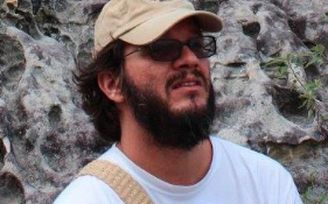Retrato do biólogo Felipe Melo, que veste boné, óculos escuros e camiseta branca
