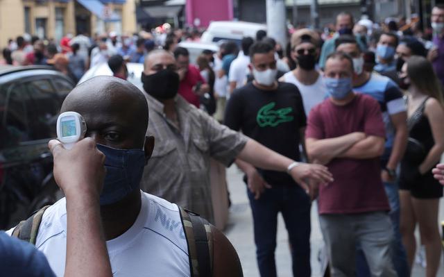 Em primeiro plano, homem aguarda a aferição de sua temperatura. Em segundo plano, outro homem estica o braço para controlar o fluxo de pessoas que, em fila, aguardam sua vez.