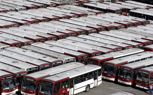 Cerca de 50 ônibus estacionados lado a lado em garagem de ônibus