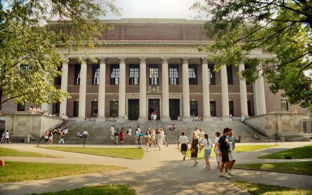 Alunos andam em frente e sobem as escadas do prédio da biblioteca Harry Elkins Widener em dia ensolarado.