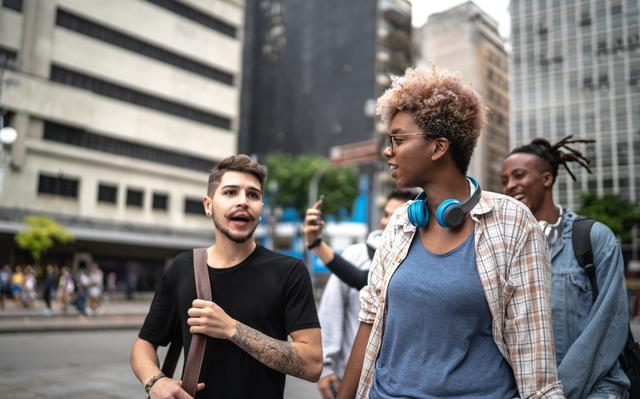 Grupo de quatro jovens andando na rua e interagindo entre si. Ao fundo vê-se prédios