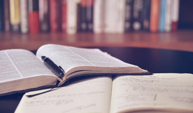 sobre mesa da madeira estão dois livros abertos, um deles com uma caneta no meio. não é possível ler o que está escrito nas páginas. Ao fundo, desfocados, estão outros livros enfileirados em uma prateleira