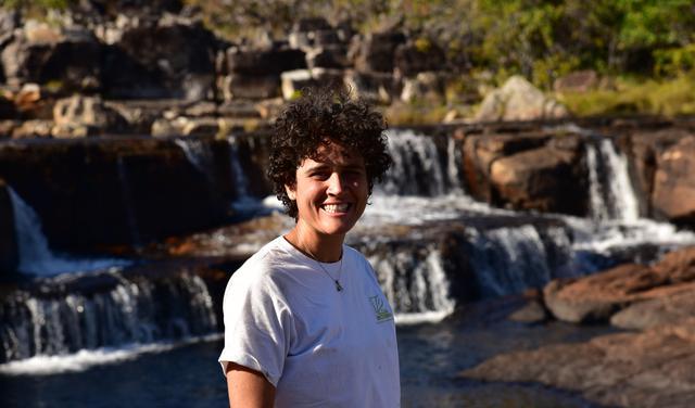 Professora Michele Dechoum, vestindo camiseta branca, sorri para foto em frente a quedas d'água