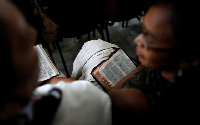 Mulher negra sentada em cadeira com bíblia aberta no colo olha para homem sentado ao seu lado