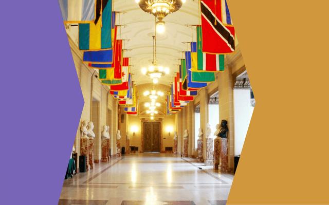 Em corredor estão dispostas estátuas de bustos junto às paredes e bandeiras de diversos países estão pendendo do teto