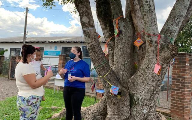 pessoas com máscaras amarram trabalhos manuais infantis em tronco de árvore