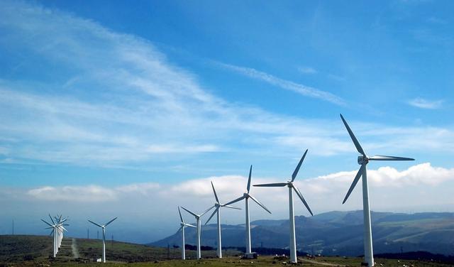 Fila de aerogeradores em paisagem natural com céu azul