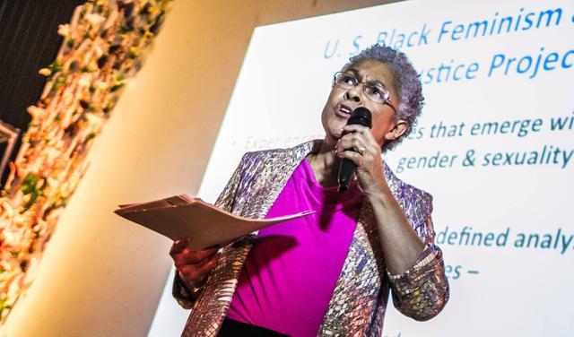 A socióloga Patricia Hill Collins se apresenta segurando microfone em frente a tela de projeção com pontos principais da sua fala