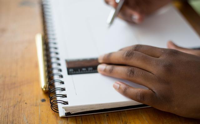 mãos traçam linha em caderno com régua e caneta
