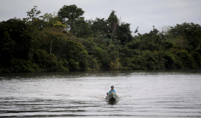 Homem senta sozinho em barco navega pelo rio xingu