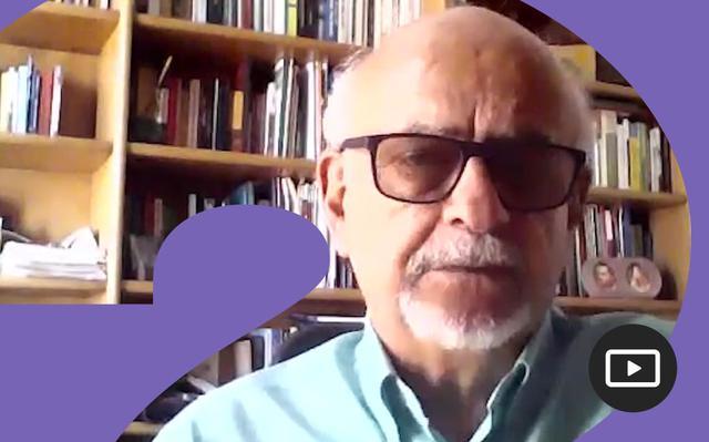 Captura do vídeo onde Renato Maluf aparece dos ombros para cima, vestindo camisa azul clara e óculos de armação preta.