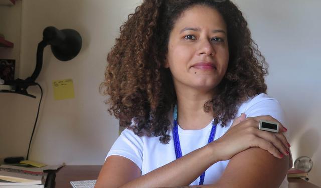 Retrato da pesquisadora Silvia Aguião, que veste camiseta branca e está com os cabelos soltos e cacheados na altura dos ombros.