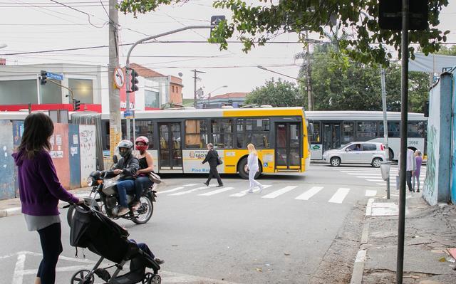 Rua perpendicular a avenida movimentada onde circulam ônibus, carros e pedestres. Em primeiro plano, mulher vestindo roupas esportivas anda com carrinho de bebê. Ao fundo, motociclista com passageira na garoupa.