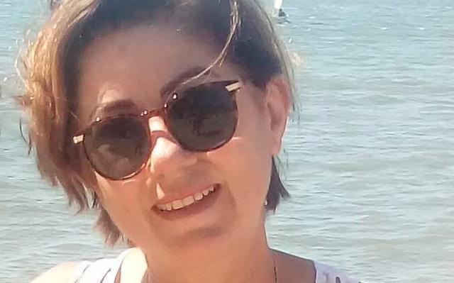 Foto da professora Sílvia Helena Zanirato, que tem cabelos curtos, veste regata branca e óculos escuros arredondados