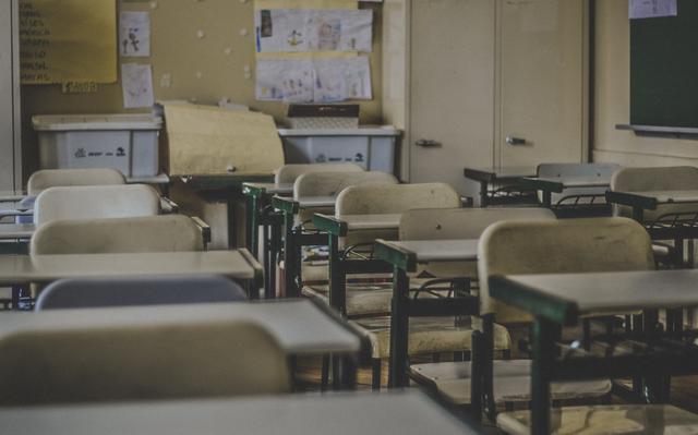 Carteiras escolares brancas em sala de aula vazia
