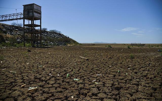 Área de reservatório seca, com solo arenoso e lixo plástico espalhado