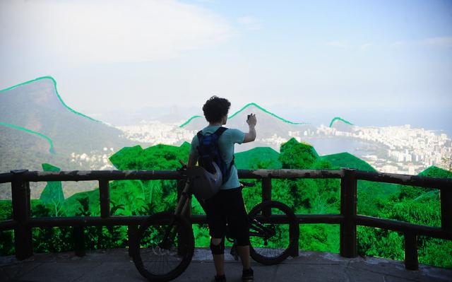 Jovem ciclista contempla paisagem do rio de janeiro do alto de uma plataforma