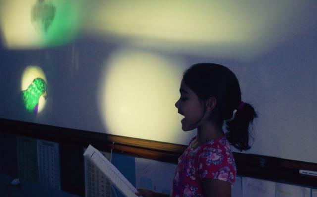 Menina vestindo camiseta florida é vista de lado lendo em voz alta conteúdo de folha de papel que tem em mãos. Ao fundo, é projetada imagem de papagaio de peito roxo.