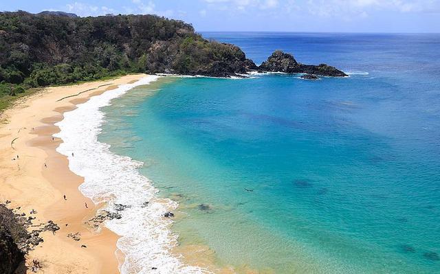 Visão aérea de praia brasileira. O mar toma a maior parte da imagem. À esquerda está faixa de aria e encosta de morro.