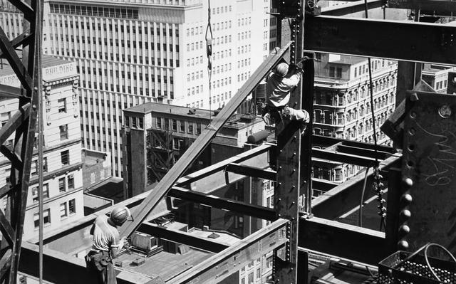 em preto e branco, dois homens trabalham sobre vigas de construção