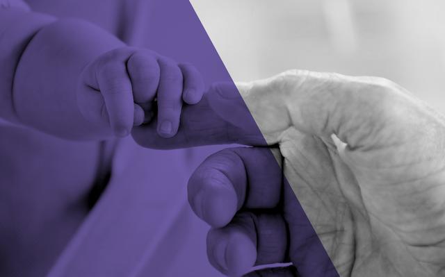 Imagem em preto-e-branco de mão de bebê segurando a mão de um idoso. Há um filtro roxo sobre parte da foto.
