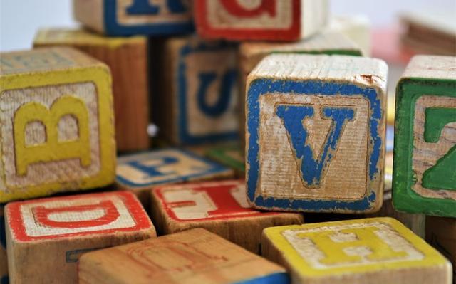 Blocos de madeira empilhados. Neles, há letras do alfabeto coloridas.