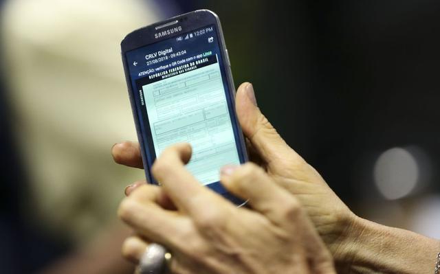 """Um celular, nas mãos de uma pessoa, exibe na tela os dados de uma carteira de motorista digitalizada. No topo, lê-se """"CLRV digital""""."""