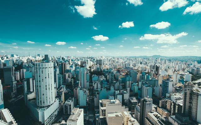 A paisagem de São Paulo vista do alto. Há muitos prédios e o céu está azul.