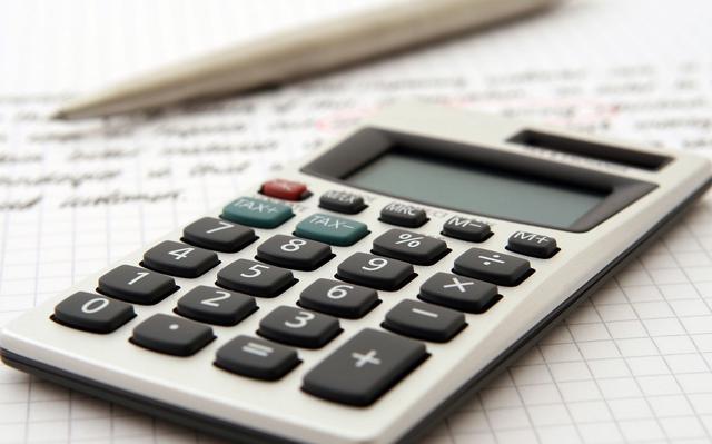 calculadora simples sobre folha de papel quadriculado com anotações desfocadas