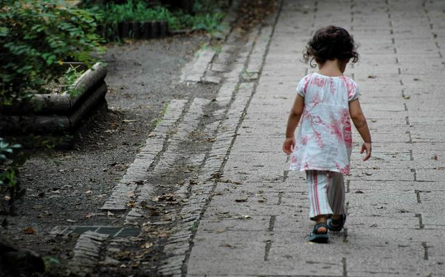 criança vista de costas anda sozinha em trecho pavimentado ao lado de terreno de terra com algumas plantas