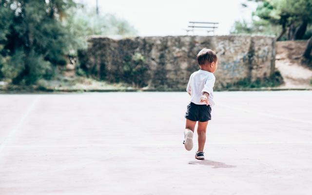 menino vestindo shorts azul e camiseta branca corre em chão cimentado