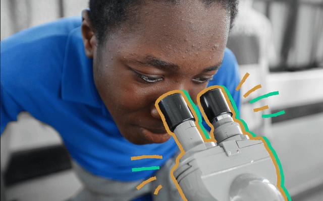 homem negro vestido de azul olha pelas lentes de um microscópio