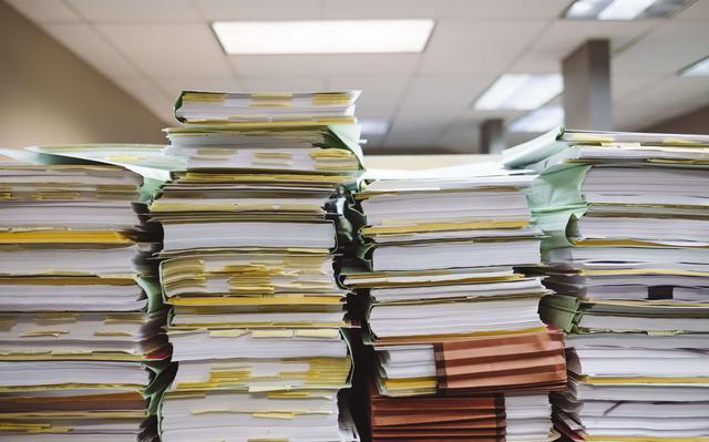 pilhas de livros com papeis e post-its marcando páginas