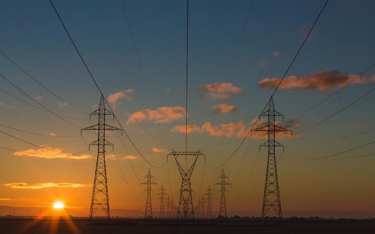 torres de transmissão de energia. ao fundo, céu em tons de azul a laranja