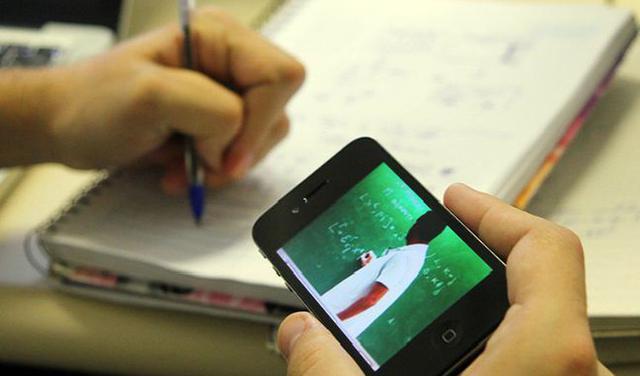 Tirada no ângulo das mãos, foto mostra que alguém segura o celular com a mão direita e uma caneta com a esquerda. A pessoa faz anotações em um caderno. Na tela do celular, vê-se a imagem de um professor em frente a uma lousa.