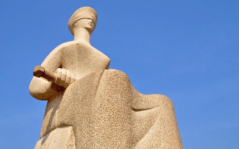 fotografada de baixo para cima, estatua de mulher vendada sentada com um espada no colo