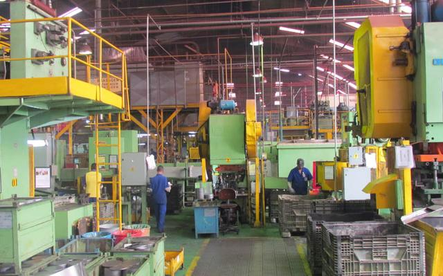 operários trabalham em maquinário de fábrica de extintores de incêndio