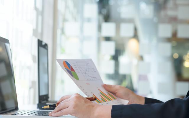 pessoa sentada em frente a um computador segura folha de papel com gráficos impressos
