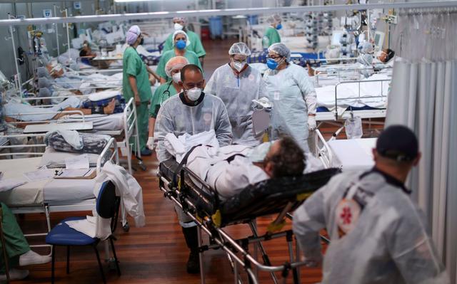 profissionais de saúde atendem pacientes em leitos de hospital de campanha. em primeiro plano, outros enfermeiros empurram maca com homem usando máscara