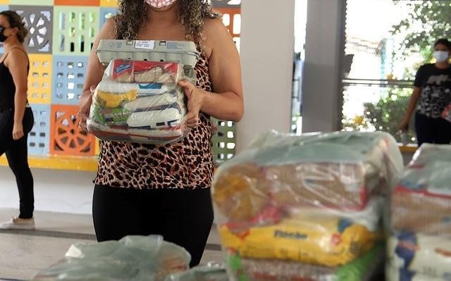 Mulher segura pacote plástico com alimentos dentro
